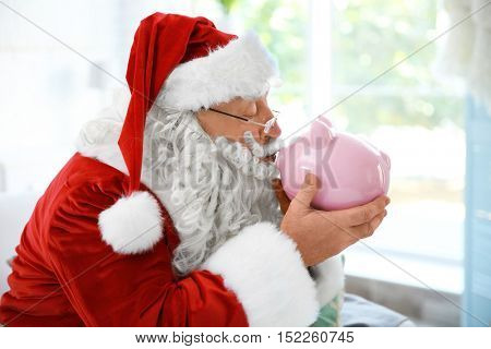 Santa Claus with piggy bank at home