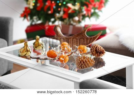 Mandarins and cones on table in decorated room