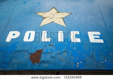 Close up white police word and yellow star on body of old blue police car.