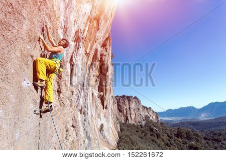 Mature male extreme Climber moving up on red orange vertical high natural rocky Wall blue clear Sky  sunshine weather