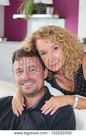 Middle-aged Couple Relaxing On Sofa At Home