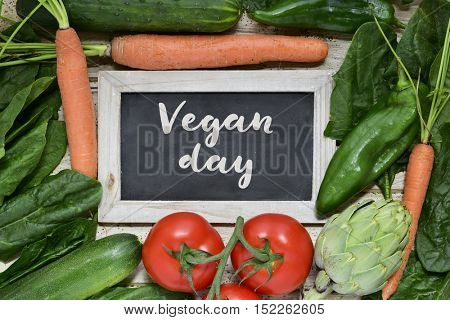 high-angle shot of a wooden surface full of different raw vegetables and a chalkboard with the text vegan day written in it