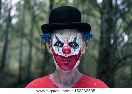 closeup of a scary evil clown wearing a bowler hat in the woods
