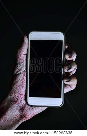 closeup of a scary and bloody hand holding a smartphone with a black blank space in its screen, against a black background