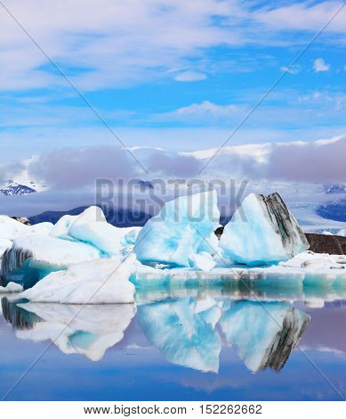 Icebergs and ice floes are reflected in smooth water. Iceland in July. Ocean ice lagoon Yokulsarlon