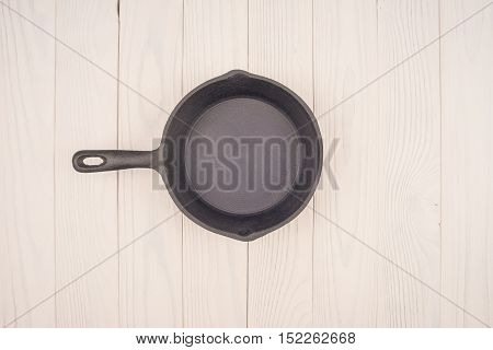 Empty pan on wooden deck table with tablecloth. Flat mock up for design. Top view.
