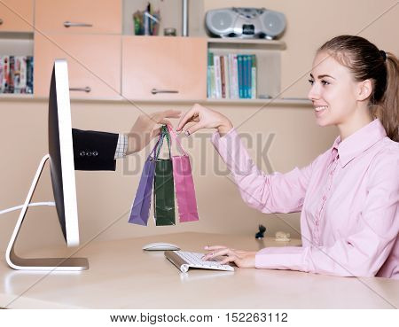 Internet Shopping and fast Delivery young Woman makes Order at Computer and Hand of Agent appears from Screen instantly completing the Deal Home Interior Background
