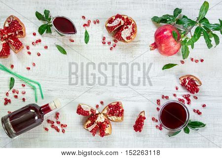 Pomegranate on a branch with leaves broken pomegranates seeds leaves gravy boat bottle straws on a light wooden background. Pomegranate fruits seeds and sauce juice. Horizontal. Top view