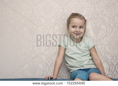 A naughty girl of six with a side gaze sitting on a sofa against the wall indoor cropped portrait