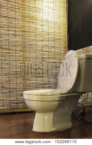 White toilet bowl with bamboo weave curtain background