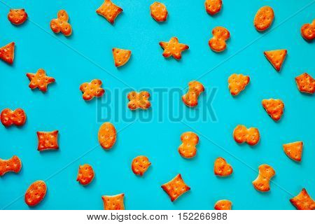 Fresh cookies crackers laid out on the bright blue surface top view