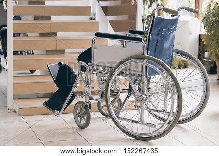 Empty Wheelchair And Stairs. Disabled Accessibility Reality.