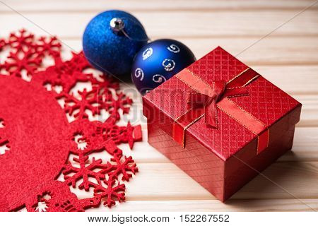 Chrismas balls, gift box and decorations on a wooden background