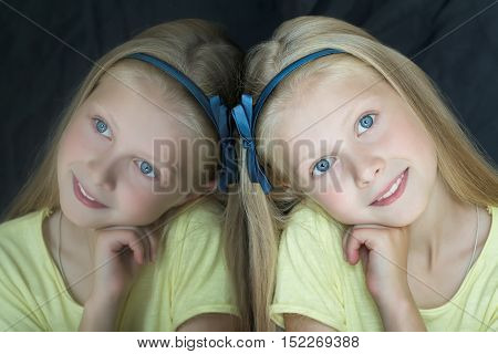 Head and shoulders indoor portrait with glass reflection of teenage blonde cute girl