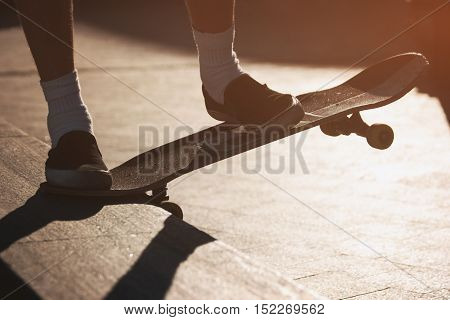 Feet on skateboard. Skateboarder is grinding. Keep the balance. Hobby of today's youth.