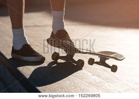 Feet and a skateboard. Legs of standing person. Make another attempt. Progress demands motivation.