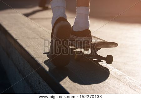 Legs riding on skateboard. Foot of skateboarder pushing ground. Brake the rules. Motion and speed.