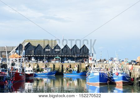 Whitstable United Kingdom -October 1 2016: Fishing Boats in Whitstable Harbour with row of warehouses in background