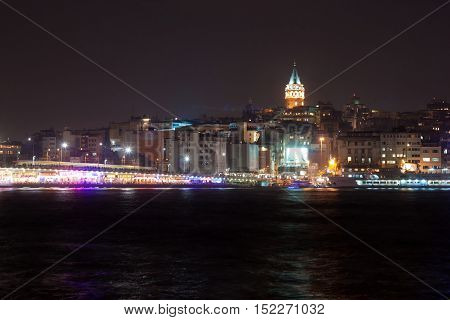 TURKEY ISTANBUL - NOVEMBER 06 2013: Night view of Galata tower near Borphorus and Galata bridge in Istanbul. The Galata Tower is a medieval stone tower in the Galata quarter of Istanbul Turkey just to the north of the Golden Horn.