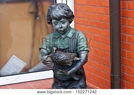 RUSSIA ZELENOGRADSK - OCTOBER 11 2014: Sculpture of a boy with bird in the Zelenogradsk promenade. Zelenogradsk (Cranz) is a resort town in Kaliningrad Oblast Russia near the Curonian Spit on the Baltic Sea.