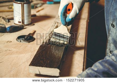 Man carpenter color brown paint wooden plank in his home workshop