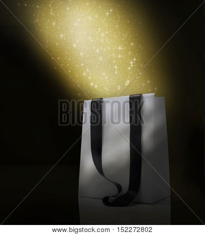 Fantasy Christmas shopping bag . Stardust  effect on awhite bag. Black background and copy space