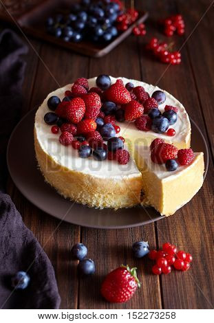 Homemade cheese cake with strawberry and winter berries. New York Cheesecake cake. Christmas dessert. Healthy food. Creative atmospheric decoration.