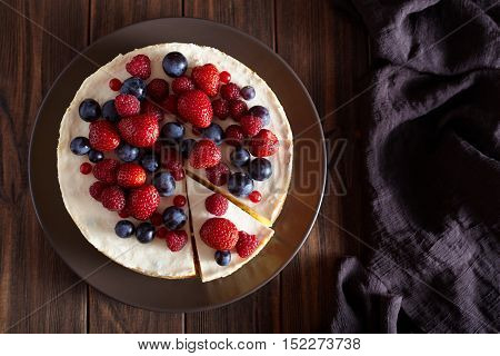 Delicious Homemade creamy mascarpone New York Cheesecake. Top viev. Cheese cake with berries on dark wooden table. Cream mousse dessert.