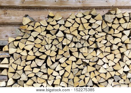 Chopped and stacked dry firewood that is stacked at wall of house in Zakopane