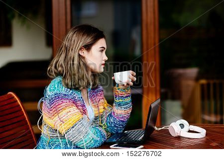 Young Woman In Colorful Woolen Sweater Drinking Coffee