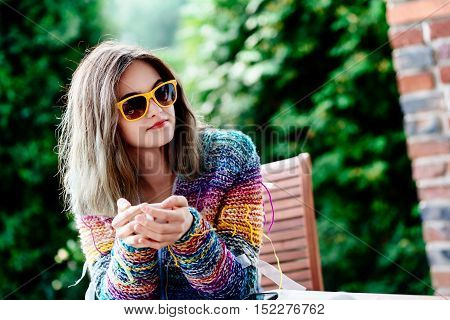Young woman in colorful woolen sweater drinking coffee or tea on the terrace.