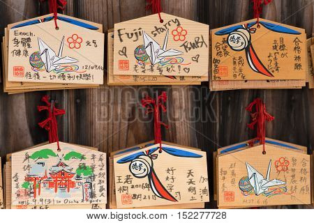 Kyoto Japan - September 17 2016: Closeup of six wooden prayer boards at Fushimi Inari Taisha Shinto Shrine. Left by worshipers writing down their wishes and pleas for the spirits of the ancestors.