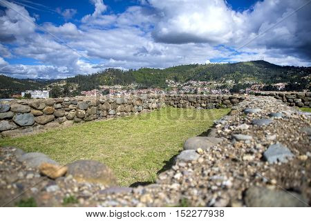 Stone walls of the ancient ruin city of Pumapungo, with the city of Cuenca, Ecuador, in the background, on a sunny morning