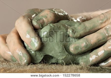 hands of ceramist kneading raw blue clay
