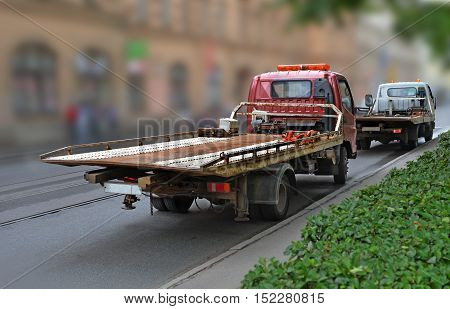 Tow truck with empty platform moves on blur to city street after other evacuator