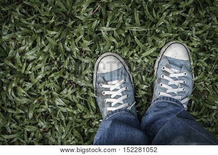 Canvas sneakers on green grass. Old blue canvas sneakers on grass. Top view of shoes on green grass in vintage tone. Dark edged.