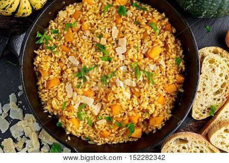 Pumpkin risotto in iron pan with Parmesan cheese, bread.