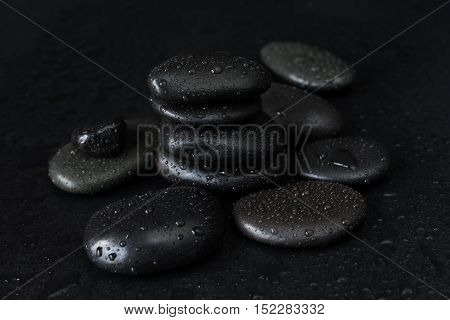 Spa concept with heap of the black basalt massage stones covered with water drops on a black background