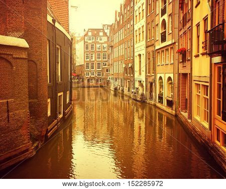 Netherlands. Amsterdam. Ancient picturesque canal in the background ancient architecture at sunset.
