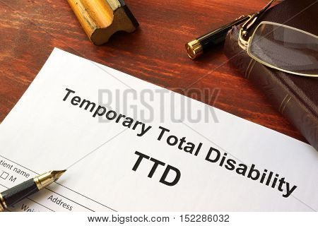 Temporary Total Disability (TTD) form on a wooden table.