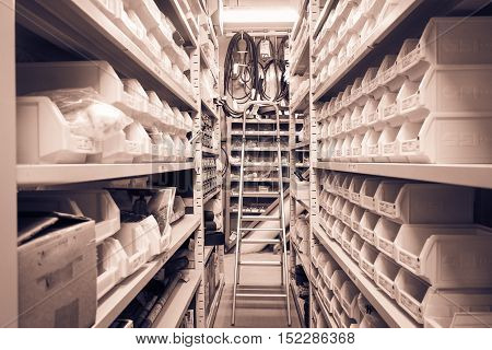 Interior of warehouse or store room Rows of shelves with boxes and basket for equipment in sepia tone.