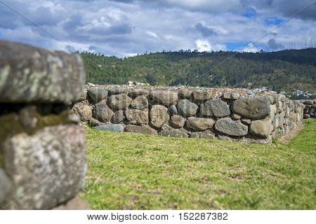 Stone walls of the ancient inca ruin city of Pumapungo, in Cuenca, Ecuador, on a sunny morning