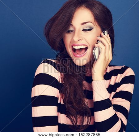 Happy Excited Woman Talking On Mobile Phone With Wide Opened Mouth On Blue Background
