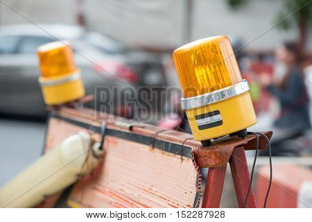 Rotating warning lights direct traffic away from a construction site. Construction and industrial objects concept.