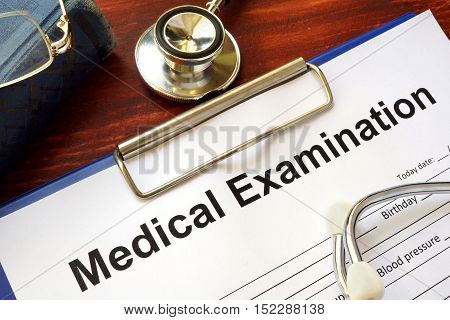 Medical Examination form on a wooden table.