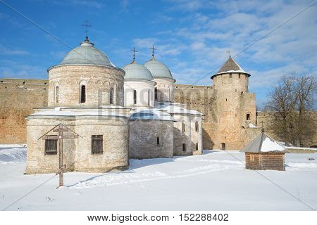 Ancient Orthodox churches and Ivangorod fortress Gate tower, sunny March day. Ivangorod, Russia