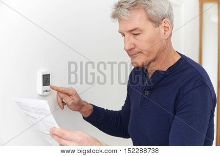 Worried Mature Man With Bill Turning Down Heating Thermostat
