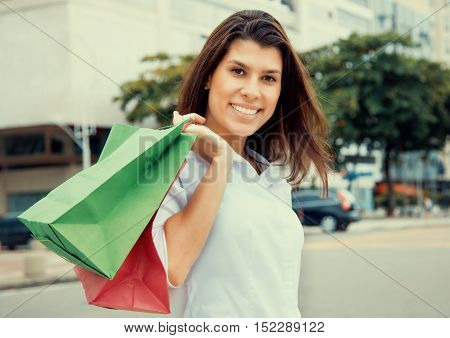 Happy woman with shopping bags in city in vintage cinema look