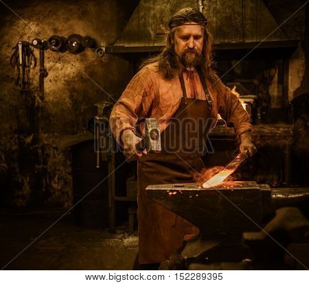 Senior blacksmith forging the molten metal on the anvil in smithy