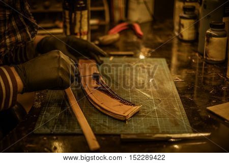 Blacksmith makes leather cover for axe